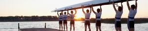 Rowing team with shell raised overhead on dock